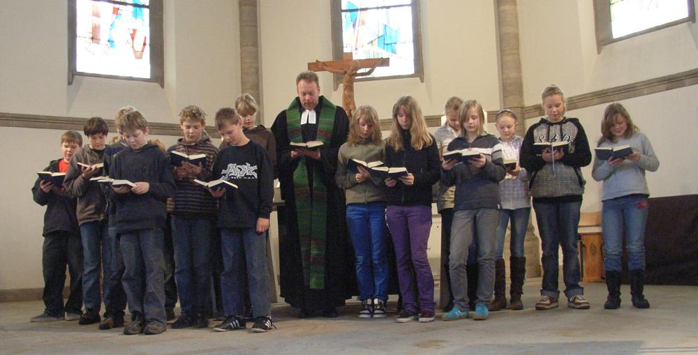 Konfis stehen am Altar der Garnisonkirche und lesen gemeinsam mit Pastor Hennings den Psalm; Bild: Kirchengemeinde Oldenburg